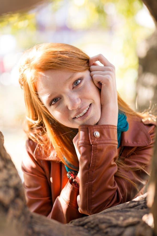 Mujer joven linda alegre positiva que presenta cerca de árbol en parque fotografía de archivo libre de regalías