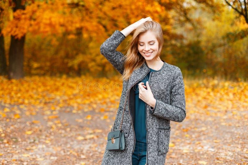 Mujer joven linda bonita alegre con una sonrisa dulce en una capa gris de moda con una camisa verde elegante con un bolso de cuer imagenes de archivo
