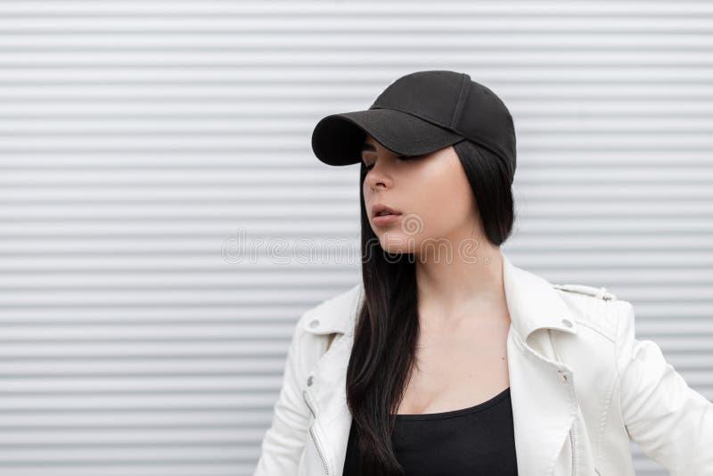 Mujer joven linda bonita en una gorra de béisbol negra de moda en una chaqueta de cuero blanca elegante en una camiseta foto de archivo libre de regalías