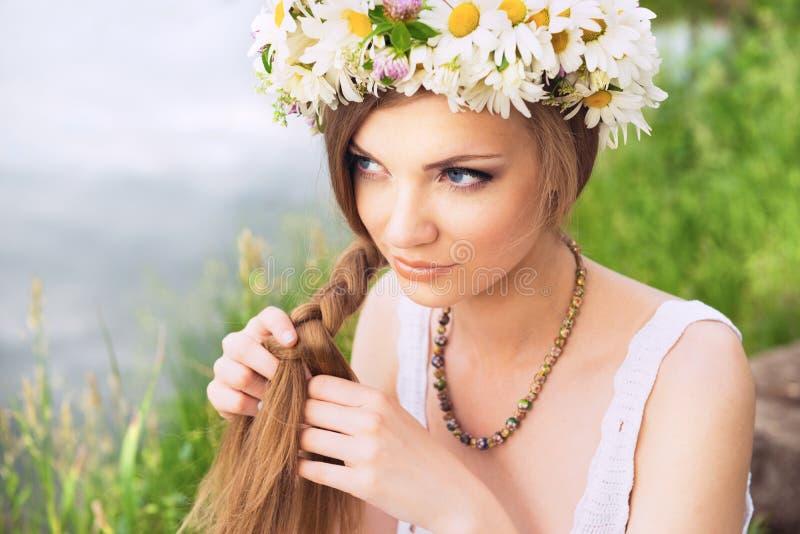 Mujer joven linda con el anillo de la manzanilla que trenza su pelo en t fotos de archivo