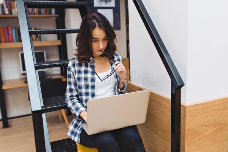 Mujer joven linda elegante que se sienta en las escaleras en la biblioteca, trabajando con el ordenador portátil Estudiando, estu fotografía de archivo
