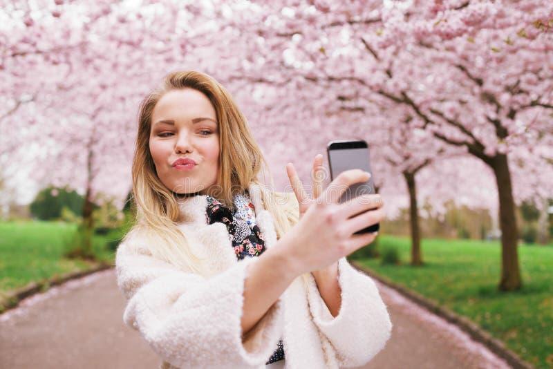 Mujer joven linda en el parque del flor de la primavera que toma el autorretrato fotos de archivo