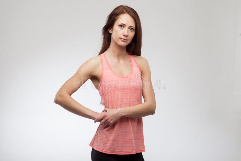 Mujer joven linda en la sonrisa de la ropa de los deportes Modelo muscular de la aptitud en fondo gris imágenes de archivo libres de regalías