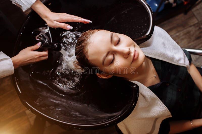 Mujer joven linda magnífica que disfruta del masaje principal mientras que peluquero profesional que aplica champú su pelo Ciérre imagenes de archivo