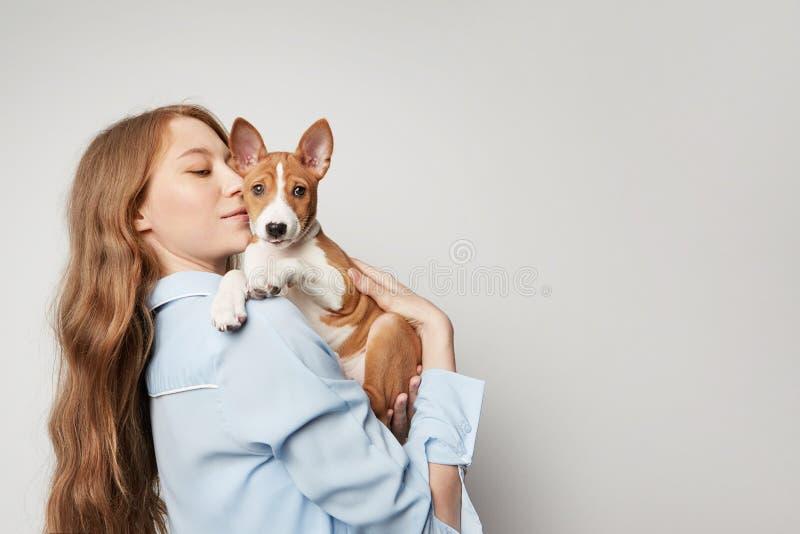 Mujer joven linda que abraza y que besa su perro del basenji del perrito Amor entre el perro y el dueño Aislado en el fondo blanc imágenes de archivo libres de regalías