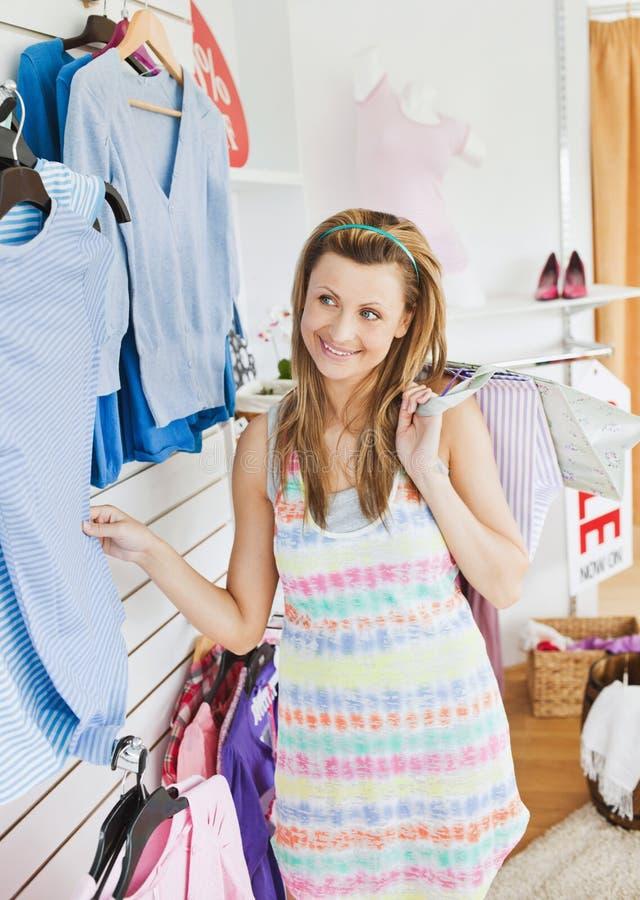 Mujer joven linda que elige la ropa en un departamento fotos de archivo libres de regalías