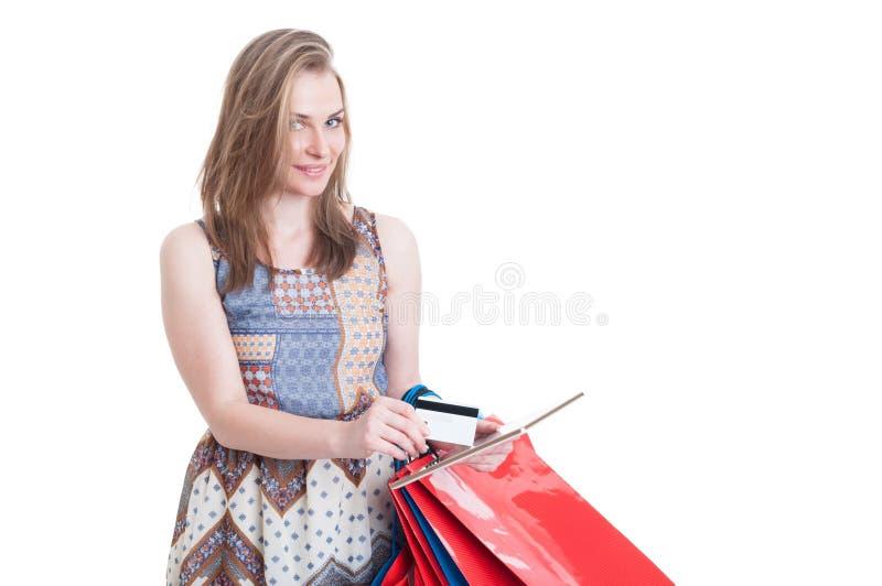 Mujer joven linda que hace compras en línea con la tarjeta y la tableta de crédito foto de archivo