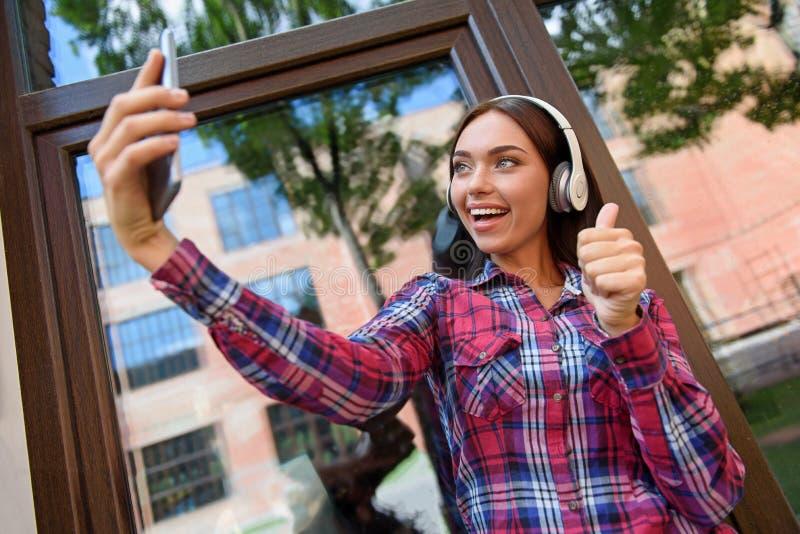 Mujer joven linda que hace el selfie en smartphone fotografía de archivo