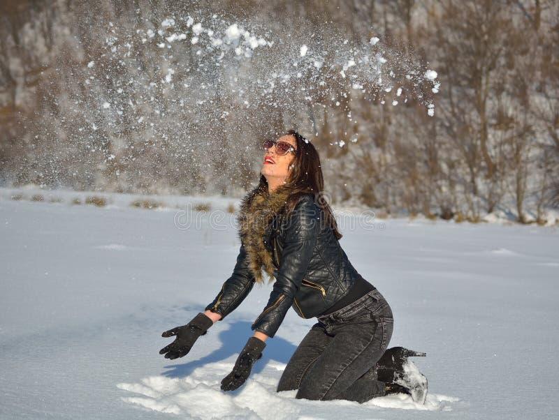 Mujer joven linda que juega con nieve fotografía de archivo libre de regalías