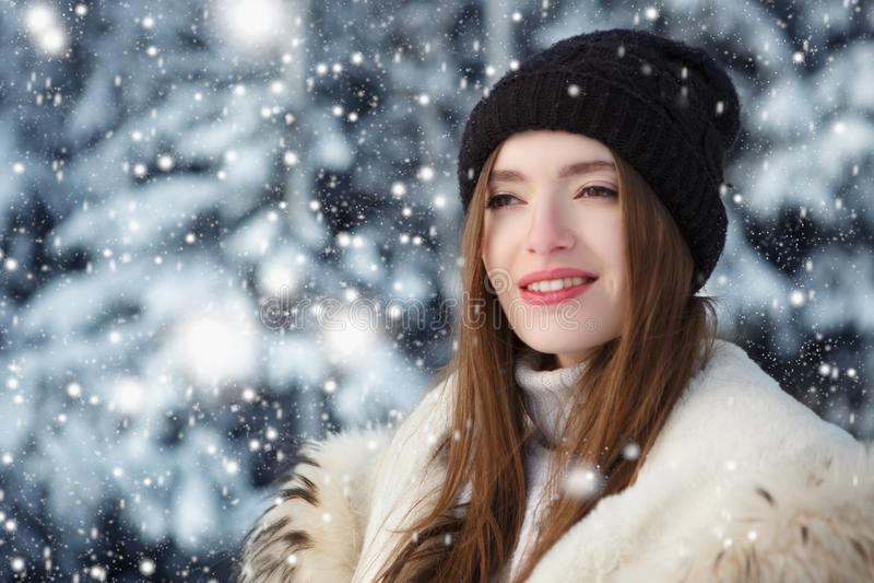 Mujer joven linda que juega con nieve en abrigo de pieles al aire libre imágenes de archivo libres de regalías