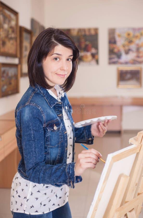 Mujer joven linda que pinta una imagen cerca de un caballete en un estudio imagen de archivo libre de regalías