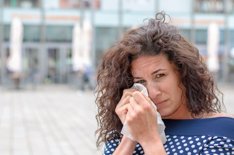 Mujer joven llorosa que la limpia ojos foto de archivo libre de regalías