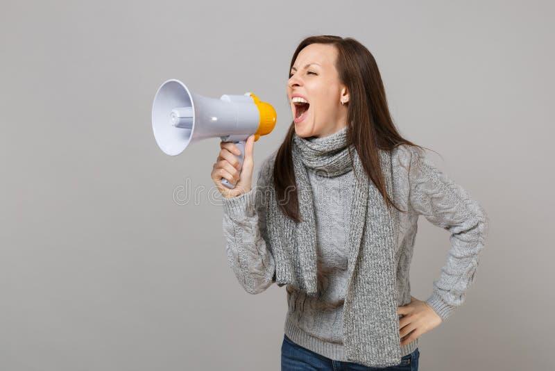 Mujer joven loca en el suéter gris, grito de la bufanda en el megáfono aislado en el fondo gris, retrato del estudio Sano fotografía de archivo