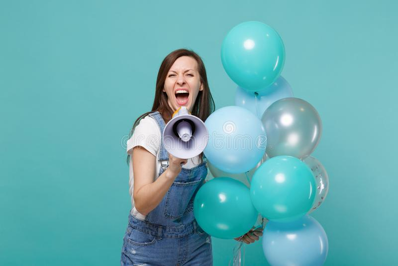 Mujer joven loca en ropa del dril de algodón que grita en megáfono, celebrando y sosteniendo los balones de aire coloridos aislad fotos de archivo libres de regalías