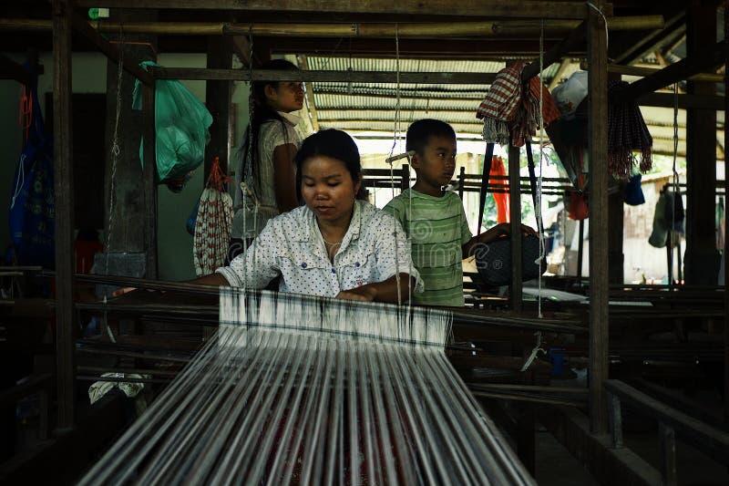 mujer joven local usando un telar tradicional con sus niños fotografía de archivo