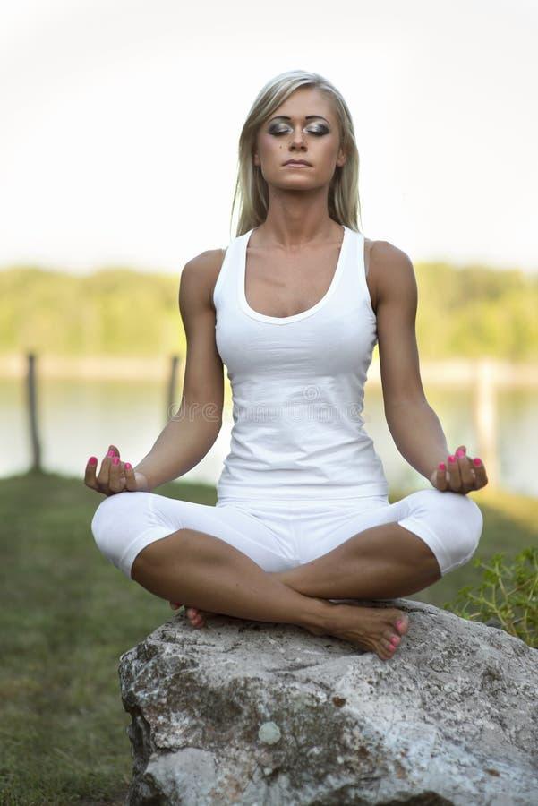 Mujer joven Lotus Yoga Position en roca fotografía de archivo