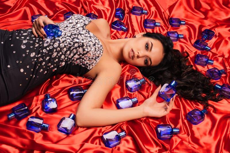 Mujer joven lujosa hermosa en un vestido brillante que presenta en el satén rojo rodeado por las botellas de perfume fotos de archivo