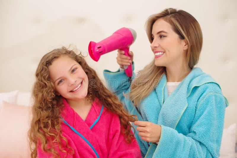 Mujer joven magnífica con su hija mientras que ella está sosteniendo un secador de pelo Chica joven adorable que presenta con su  foto de archivo libre de regalías