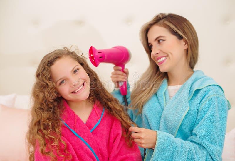 Mujer joven magnífica con su hija mientras que ella está sosteniendo un secador de pelo Chica joven adorable que presenta con su  fotos de archivo