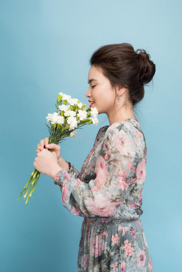 Mujer joven magnífica en vestido retro lindo sobre fondo azul imagenes de archivo
