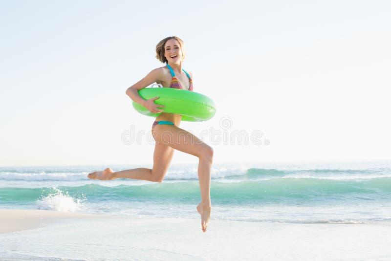 Mujer joven magnífica que lleva a cabo un anillo de goma mientras que salta en la playa fotografía de archivo