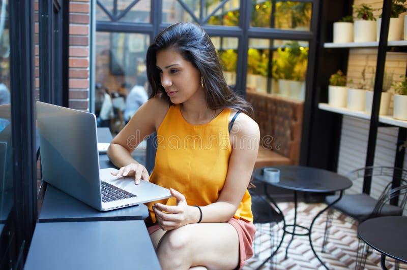 Mujer joven magnífica que se sienta con el ordenador portátil abierto en la cafetería moderna interior, freelancer de sexo femeni fotografía de archivo libre de regalías