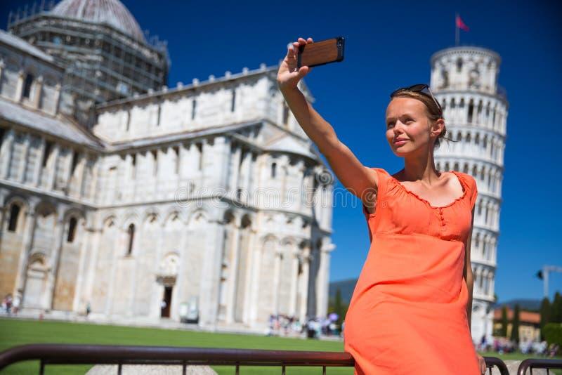 Mujer joven magnífica que toma un selfie con su teléfono elegante imagen de archivo