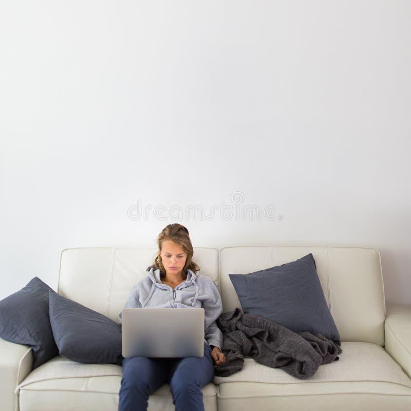 Mujer joven magnífica que usa su tableta foto de archivo