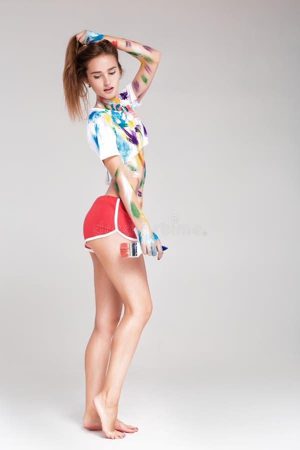 Mujer joven manchada en pintura multicolora imagen de archivo