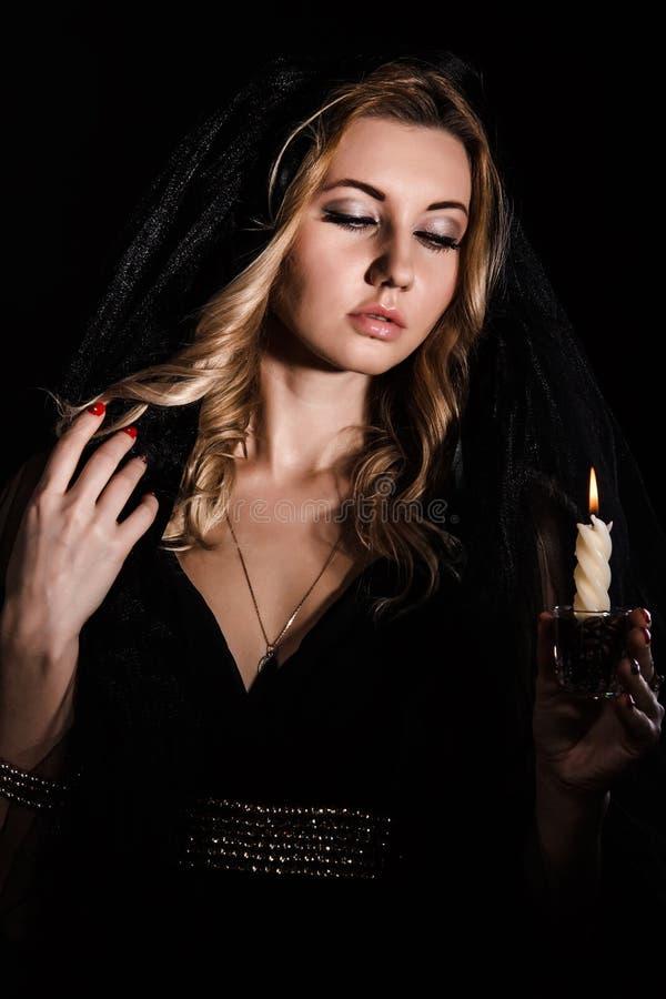 Mujer joven misteriosa con una vela imagen de archivo