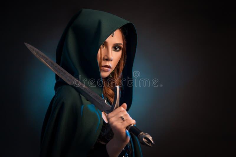 Mujer joven misteriosa que guarda el cuchillo afilado, cabo verde que lleva con una capilla fotos de archivo libres de regalías