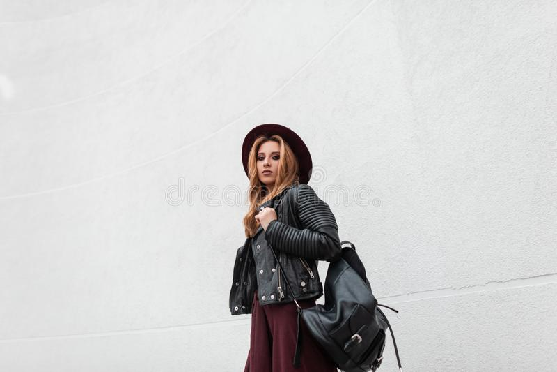 Mujer joven moderna bonita en ropa de moda con una mochila de cuero negra en un sombrero p?rpura que presenta cerca de una pared  fotografía de archivo
