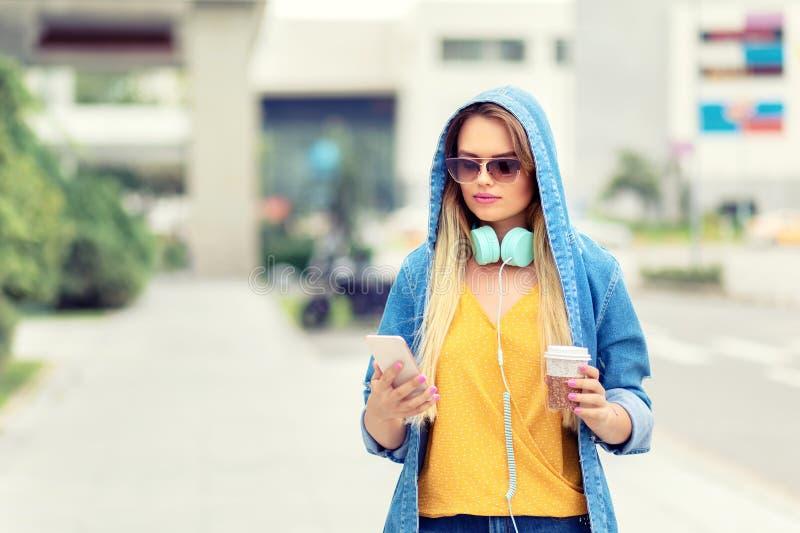 Mujer joven moderna en ciudad grande usando el teléfono móvil mientras que camina en la calle foto de archivo