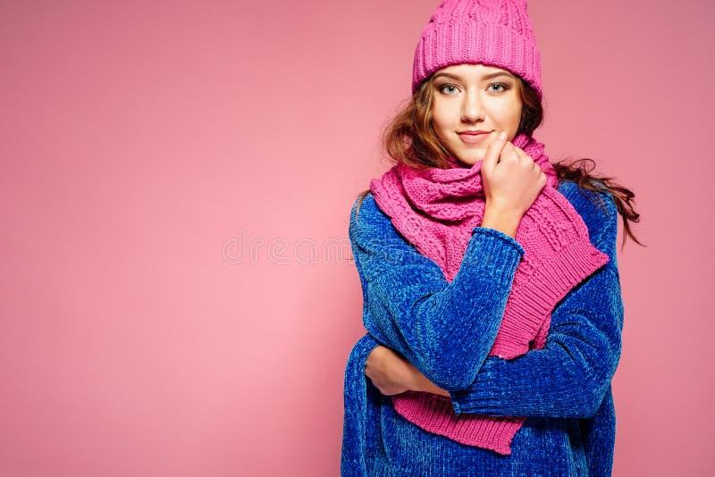 Mujer joven moderna que lleva el suéter azul y sombrero rosado, y presentación de la bufanda, haciendo la expresión facial divert imágenes de archivo libres de regalías