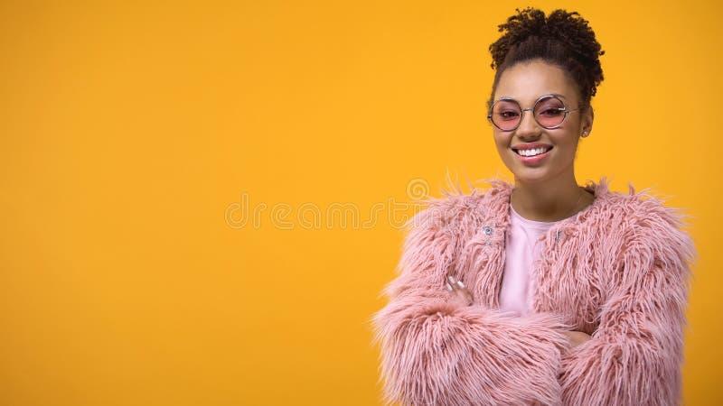 Mujer joven moderna que presenta en el fondo amarillo de la cámara, cursos del estilo, plantilla fotos de archivo libres de regalías