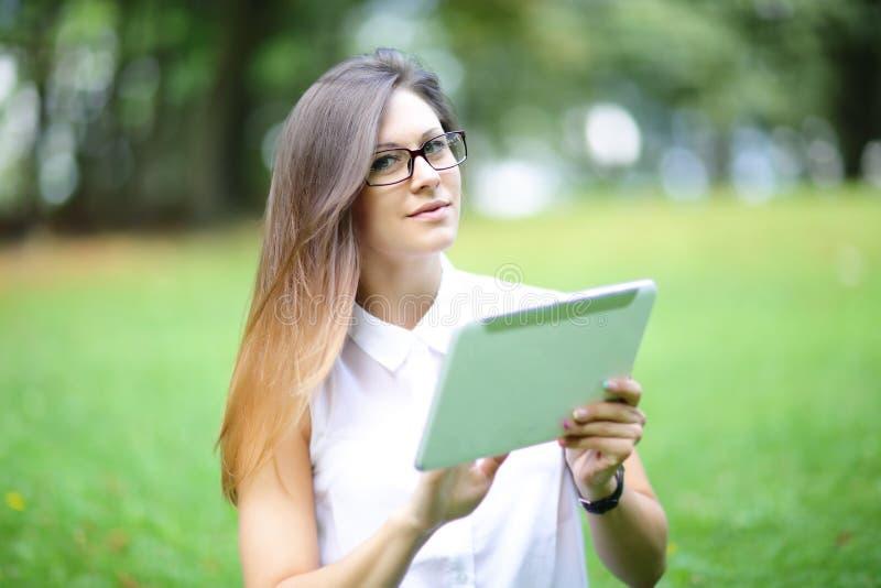 Mujer joven, muchacha que trabaja con la tableta fotografía de archivo