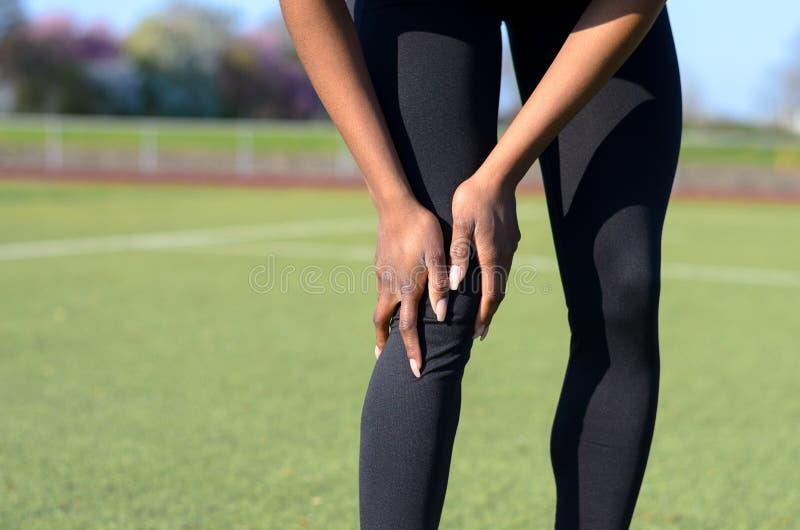Mujer joven muscular deportiva que agarra su rodilla fotografía de archivo