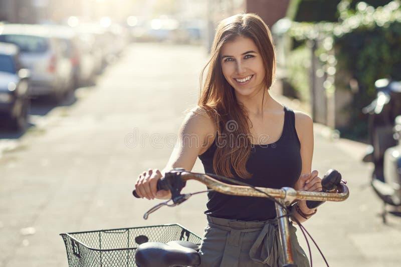 Mujer joven o estudiante amistosa atractiva con su situación de la bicicleta en una calle urbana en sol del verano que sonríe fel fotos de archivo libres de regalías