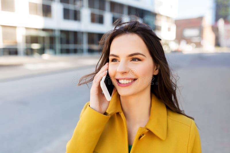 Mujer joven o muchacha sonriente que invita a smartphone imagenes de archivo