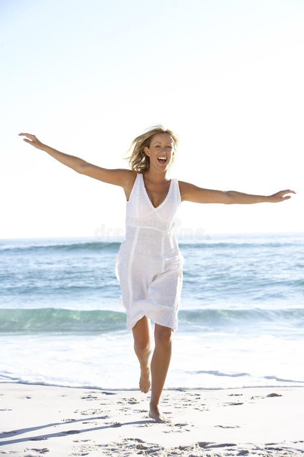 Mujer joven ocasional vestida que corre a lo largo de la playa imágenes de archivo libres de regalías