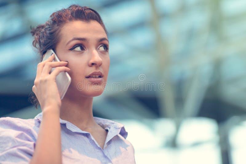 Mujer joven ocupada con la llamada, charlando en el retrato de la vista lateral del teléfono celular imagenes de archivo