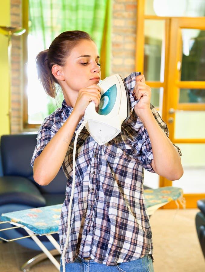 Mujer joven ocupada que plancha su ropa en uno mismo. fotos de archivo