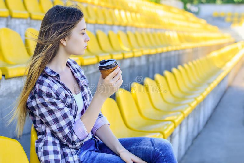 Mujer joven pacífica en camisa a cuadros con la taza de reloj del café foto de archivo
