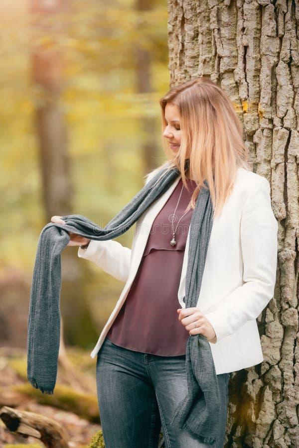 Mujer joven parada en el bosque otoñal foto de archivo libre de regalías