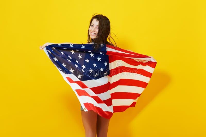 Mujer joven patriótica con la bandera americana fotografía de archivo libre de regalías
