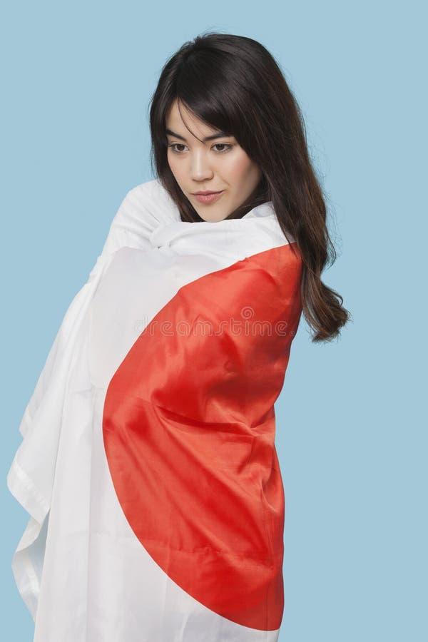 Mujer joven patriótica envuelta en bandera japonesa sobre fondo azul fotos de archivo libres de regalías