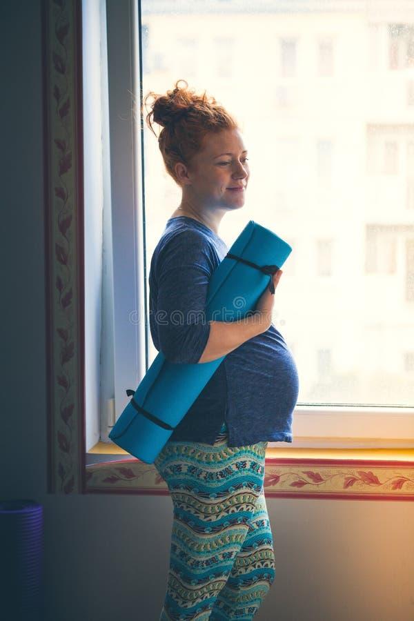 Mujer joven pelirroja embarazada antes de la clase de la yoga fotografía de archivo