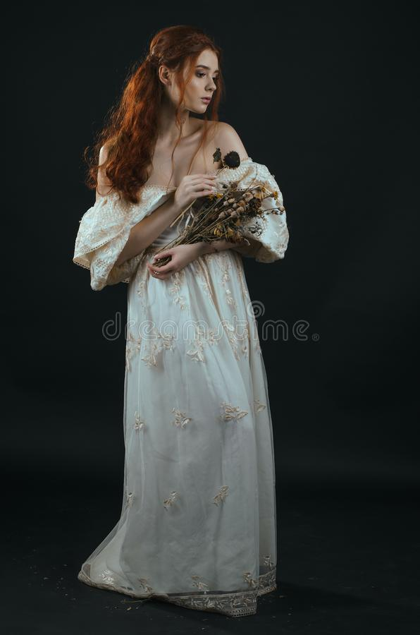 Mujer joven pelirroja en un vestido del oro del vintage con los hombros desnudos con un ramo seco en manos en un fondo negro en g imagenes de archivo