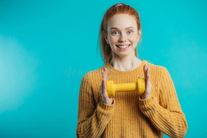 Mujer joven pelirroja linda feliz que presenta con pesa de gimnasia amarilla imagen de archivo libre de regalías