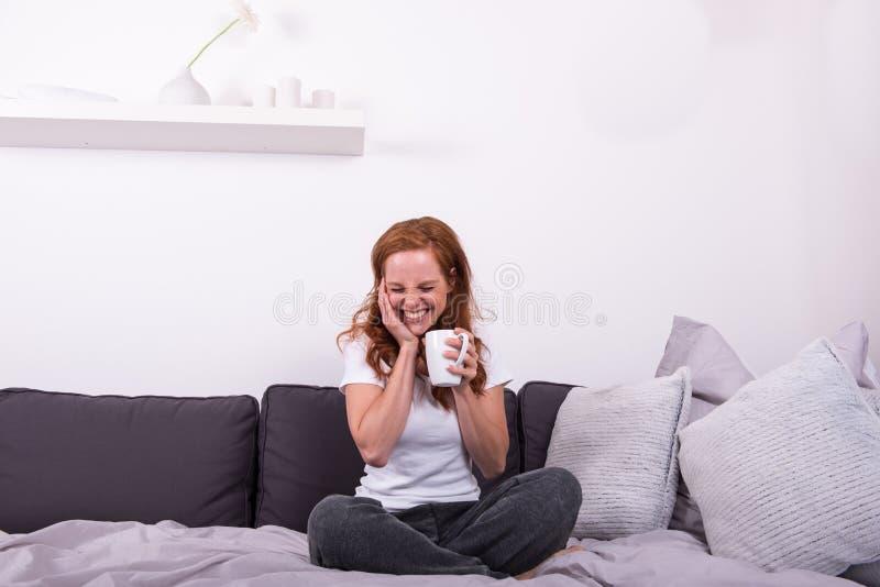 Mujer joven, pelirroja que se sienta en la cama y que disfruta de su coff fotografía de archivo libre de regalías